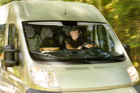cargo van: Postal delivery courier man driving cargo van delivering package