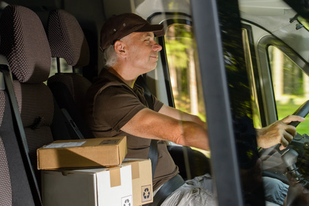 Happy postal delivery courier man driving cargo car delivering package