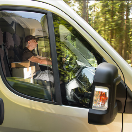 Professional courier man driving cargo car delivery postal service photo