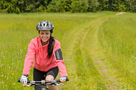 Woman riding bicycle on countryside path through meadow smiling photo