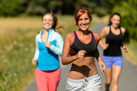 Three friends running outdoors on sunny day smiling photo