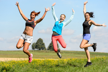 Sportive friends jumping cheerful on sunny meadow teenage girls photo