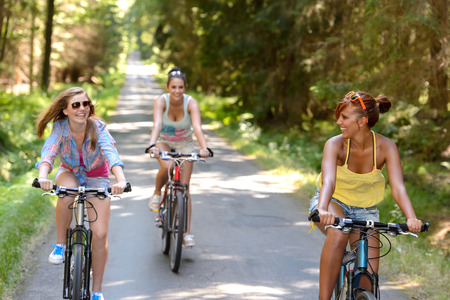 summer sport: Happy girls riding bicycles outside enjoy summer sport