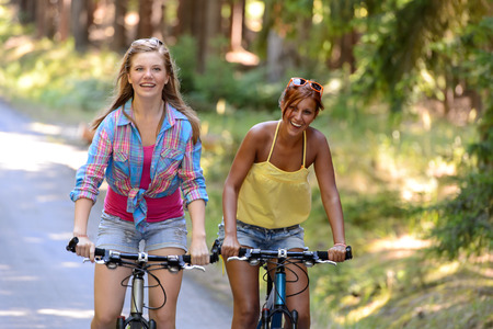 Two teenage girls riding their bikes laughing enjoy summer sport photo