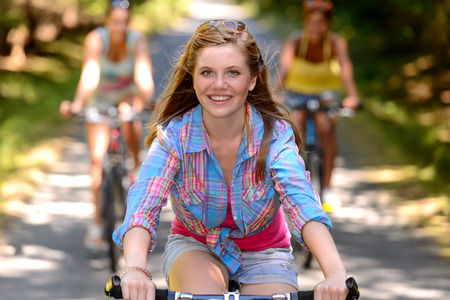 Teenage girl riding bike with friends on countryside road photo