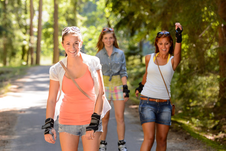 Three women friends roller skating outdoors summer park photo