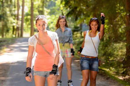 rollerskating: Three women friends roller skating outdoors summer park Stock Photo
