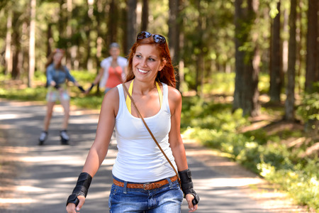 Young woman roller skating outdoors summer sport on countryside road photo