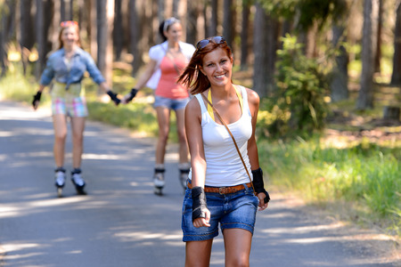 Young woman roller skating outdoors with friends summer sport photo