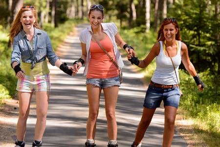 inline skater: Cheerful young women on roller skates holding hands outdoor summertime