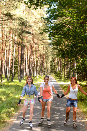 Three friends roller skating outdoor holding hands summer sport photo