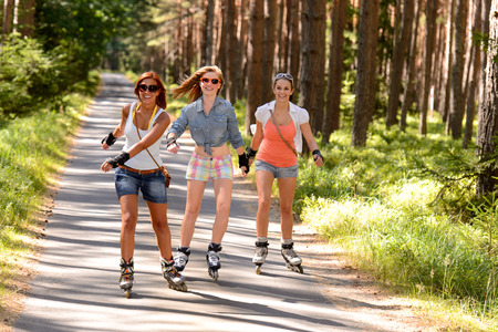 rollerskating: Three friends on in-line skates outdoor on summer countryside road