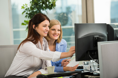 Beautiful businesswomen looking at computer monitor in office photo