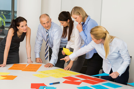 arrange: Business team discussing multicolored labels in boardroom meeting