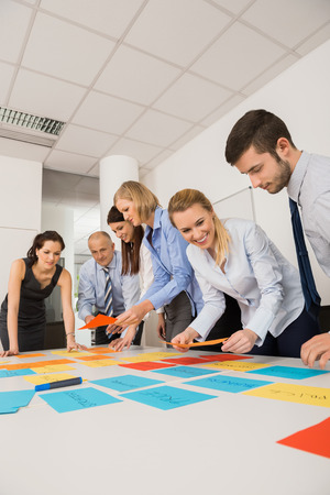 Business colleagues brainstorming with multicolored labels planning strategy in meeting photo