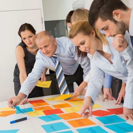 Business colleagues arranging multicolored labels on table in meeting Standard-Bild