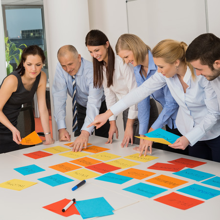 Business team brainstorming using color labels on table in office