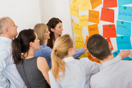 Business colleagues brainstorming multicolored labels stuck on whiteboard in meeting