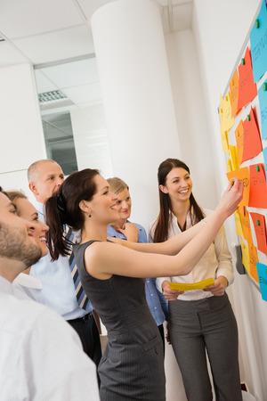 Empresaria pegando etiquetas en la pizarra durante la reunión
