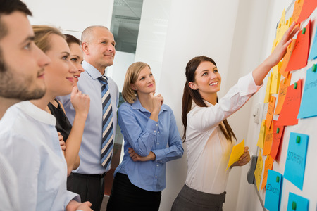 Businesswoman pointing  on whiteboard in meeting with office colleagues Banco de Imagens