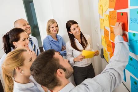 De negocios que explica las etiquetas en la pizarra a colegas en la reunión