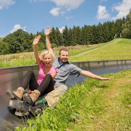 Portrait of young couple enjoying summer sledge ride photo