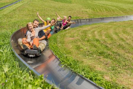 Portrait of happy young couples enjoying summer sledge ride photo