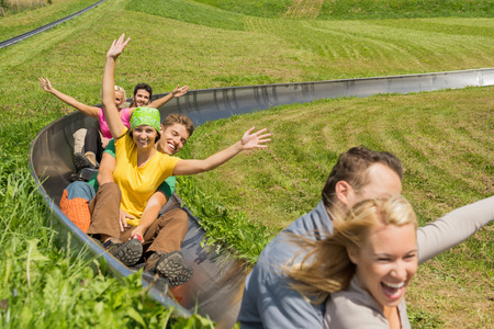luge: Excited young couples enjoying alpine coaster luge during summer