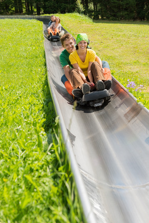 luge: Happy young couples enjoying alpine coaster luge during summer