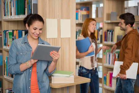 University student looking at tablet with classmates talking in library photo