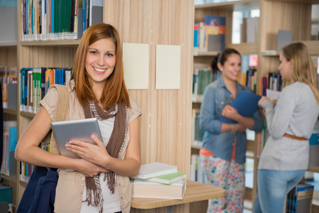Smiling college student holding tablet with friends standing in library photo