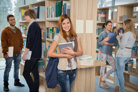 Girl holding tablet with group of students in college library photo