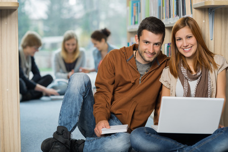 Smiling college students with laptop with classmates in library photo
