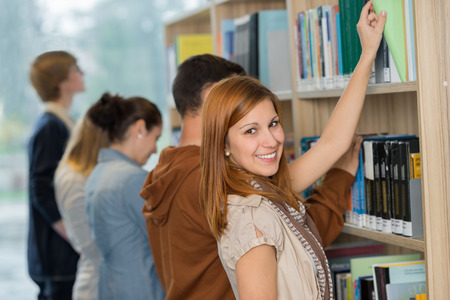 Student choosing book from bookshelf with friend in college library Imagens