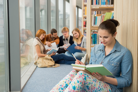 Young student sitting in college library with friends in background photo