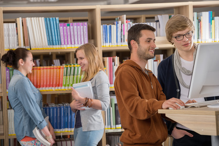 Group of young university students discussing in library photo