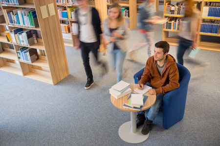 Student writing notes with classmate walking in library blur motion photo
