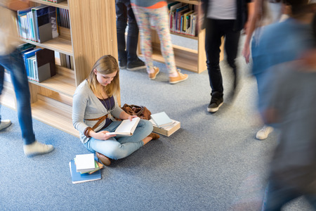 Student sitting on floor in library classmates walking blur motion photo