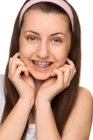 Smiling girl with braces teenager beauty on white background photo