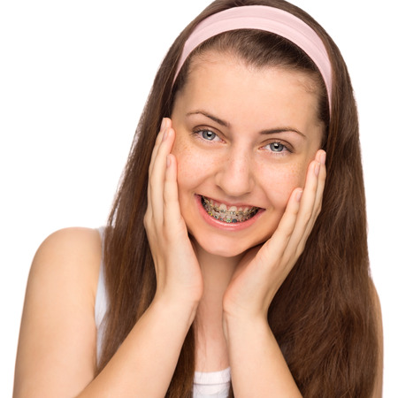 Happy girl with braces teenage beauty on white background photo