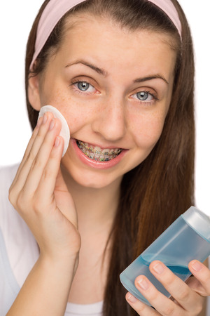 Girl with braces using makeup removal on white background photo