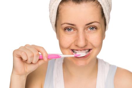 Teenage girl with braces brushing teeth on white background photo