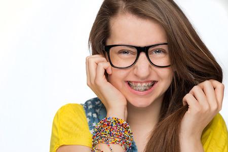 Muchacha alegre con los apoyos que usan gafas friki en el fondo blanco