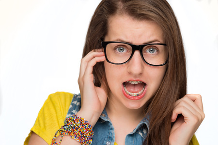 Crazy girl in braces wearing geek glasses on white background photo