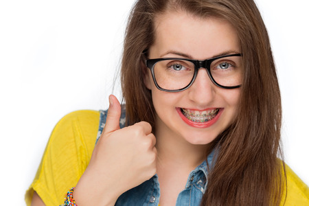 Girl with braces wearing geek glasses showing thumb up isolated