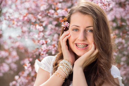 Romantic girl with braces touching cheek near blossoming tree spring photo