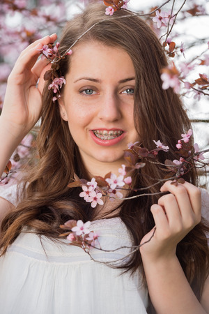 waistup: Teenage romantic girl with braces holding blossoming tree branch spring
