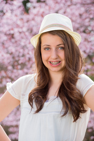 Smiling romantic girl with braces wearing hat against blossom tree photo