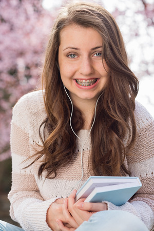 Happy teenage student with braces holding book outside photo
