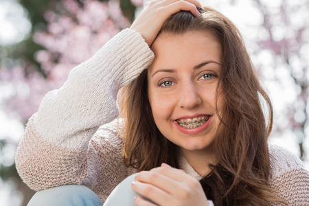 Happy girl wearing braces with hand in hair outdoors spring photo